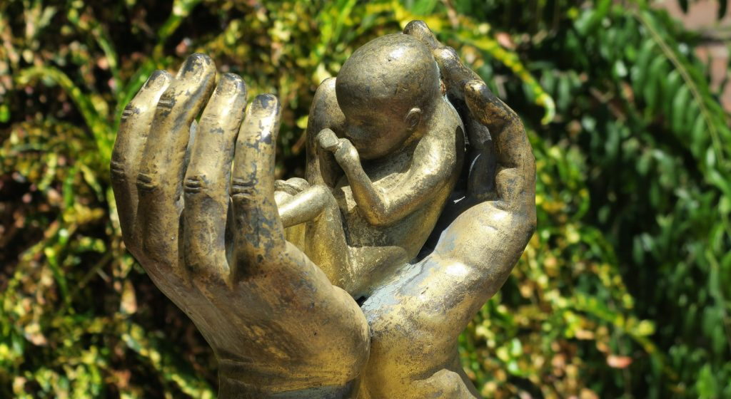 hands protecting the unborn infant